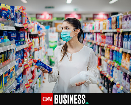 Image of a woman at the supermarket choosing a cleaning product